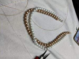 You start by creating three single strands of pearls!
