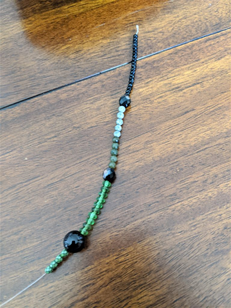 I started stringing my beads with some tiny black ones, followed by some green ones!