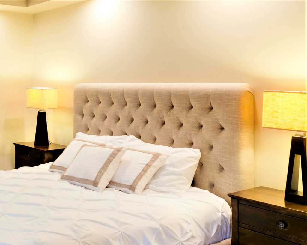 A tufted headboard like the one pictured is perfect to fill negative space in your large bedroom!