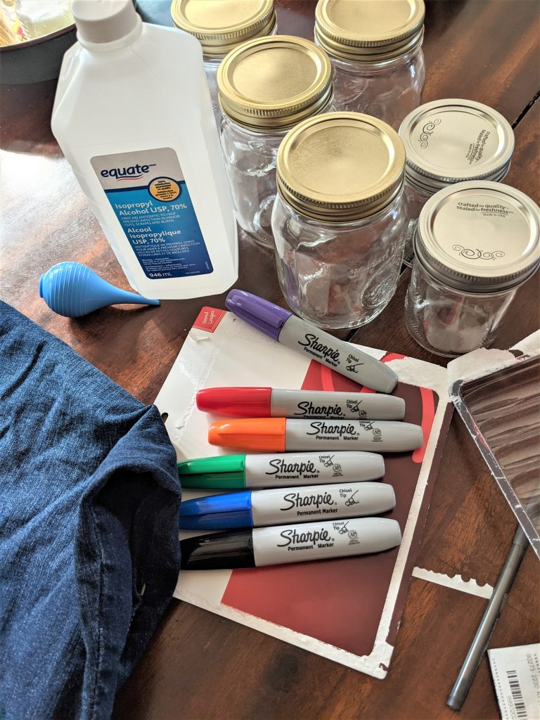 To get started making your own alcohol inks, you just need glass jars, applicator bottles, rubbing alcohol and sharpie markers!